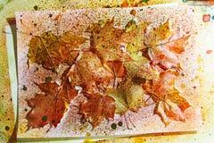 Herbsthintergrund von Blättern und Spray der Farbe Lizenzfreie Stockbilder