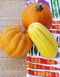 Herbstkürbis und -kürbis auf bunter Stoff- und Rattantischplatte stockfotos