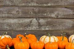 Herbstkürbise und -kürbisse gegen alten hölzernen Hintergrund Stockfotos