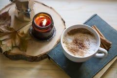 Herbstkaffee, Cappuccinoschale mit Zimt und duftende Kerze stockfotos