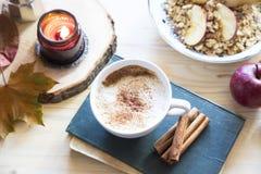 HerbstKaffeetasse, Cappuccino mit Zimt, Buch und Kerze, Fa stockbild