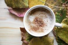 HerbstKaffeetasse, Cappuccino mit Zimt und getrocknete Blätter, zu stockfoto