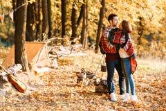 Herbstkampieren Umarmen und zwei des glücklichen Paars unter einer warmen Decke Lizenzfreie Stockfotografie