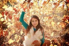 Herbstkindermädchen entspannt im Fallwald Stockfoto