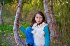 Herbstkindermädchen entspannte sich im Wald mit grünen Stöcken Stockbild