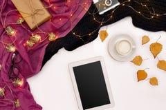 Herbstkonzept, getrocknete Fallblätter, Becher Kakao, alte Kamera, Schal und Tablette mit leerem Bildschirm Spott oben Stockfoto
