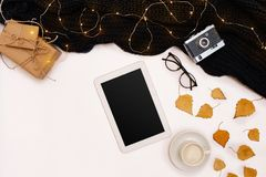 Herbstkonzept, getrocknete Fallblätter, Becher Kakao, alte Kamera, Schal und Tablette mit leerem Bildschirm Spott oben Lizenzfreies Stockbild
