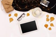 Herbstkonzept, getrocknete Fallblätter, Becher Kakao, alte Kamera, Schal und Tablette mit leerem Bildschirm Spott oben Stockbild