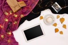 Herbstkonzept, getrocknete Fallblätter, Becher Kakao, alte Kamera, Schal und Tablette mit leerem Bildschirm Spott oben Stockfotografie