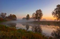 Herbstlandschaft, Bäume im Nebel an der Dämmerung Lizenzfreies Stockfoto