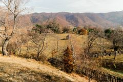 Herbstlandschaft, die ein altes traditionelles kleines Haus, umgeben durch Bäume und Berge darstellt stockfotografie
