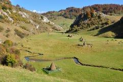 Herbstlandschaft mit Heuschobern in einem Tal Stockbilder
