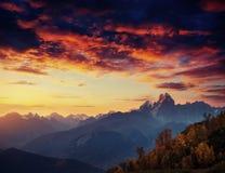 Herbstlandschaft und schneebedeckte Bergspitzen Fantastischer Sonnenuntergang vie Stockfotos