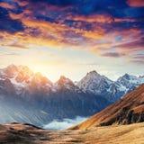 Herbstlandschaft und schneebedeckte Bergspitzen Fantastischer Sonnenuntergang vie Stockbild