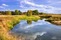 Herbstlandschaft von Fluss und Bäume und Büsche Stockfotografie