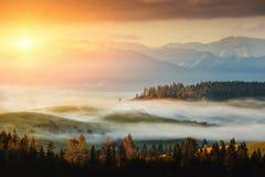 Herbstlandschaftsbild mit Sonnenaufgang oder Sonnenuntergang, schöner Nebel auf Wiese und Berg auf Hintergrund Stockbilder