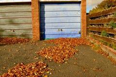 Herbstlaub durchgebrannt in Garagenblock stockbilder