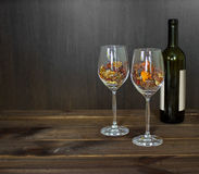 Herbstlaub in einem Weinglas und in einer Weinflasche auf Holztischhintergrund Stockfotos