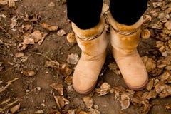 Herbstlaub und die Füße der Frau Stockfotografie