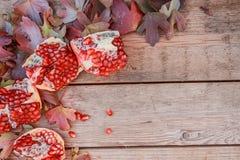 Herbstlaub und Granatapfel Reifes geschnittenes Granatapfelstillleben mit gelbem Blatt stockbilder