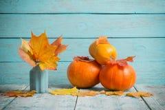 Herbstlaub und Kürbise auf blauem hölzernem Hintergrund stockfotos