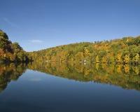 Herbstlaubreflexionen auf einem See Stockbilder