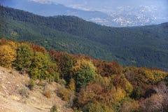 Herbstlaubwechselnde und Koniferenwälder und eine Stadt im Tal im Hintergrund Lizenzfreie Stockfotografie