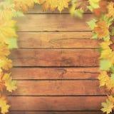 Herbstliche Blätter über altem hölzernem Schreibtisch stockfoto