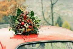 Herbstlicher Blumenstrauß auf die Oberseite des Retro- Autos Stockfoto