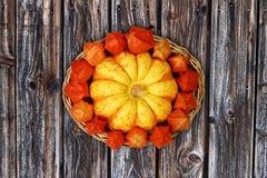 Herbstlicher Korb mit dekorativem Kürbis und Physalis auf hölzernem Hintergrund Lizenzfreie Stockfotos