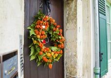 Herbstlicher Kranz mit Physalis auf einer Tür Lizenzfreie Stockfotos