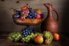 Herbstliches Fruchtstillleben mit georgischem Krug auf rustikalem hölzernem Vorsprung stockfoto