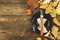 Herbstliches Gedeck für Danksagungsabendessen Leere Platte, Tischbesteck, farbige Blätter auf Holztisch Falllebensmittelkonzept lizenzfreie stockfotografie