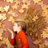 Herbstmädchen auf den getrockneten Blättern, die Windlippen durchbrennen Lizenzfreie Stockfotografie