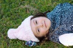 Herbstmädchen, das im Gras liegt Stockbilder