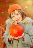 Herbstmädchen im Kürbishut Stockfoto