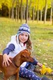 Herbstmädchen im Pappelbaumwald, der mit Hund spielt Stockfoto