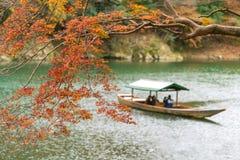 Herbstorange und -ROT, mit Booten im Hintergrund unscharf Stockbild