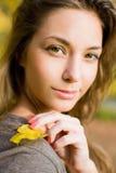Herbstpark und ein schöner Brunette. Lizenzfreies Stockfoto