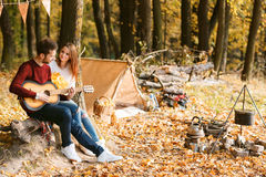 Herbstpicknick Glückliches Paar mit Gitarre nahe dem Zelt Lizenzfreies Stockbild