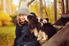 Herbstporträt des glücklichen Kindermädchens, das mit ihrem Spanielhund im Garten spielt Stockbilder