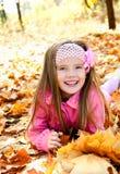 Herbstporträt des glücklichen kleinen Mädchens mit Ahornblättern Lizenzfreies Stockfoto