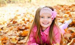 Herbstporträt des glücklichen kleinen Mädchens mit Ahornblättern Stockbild