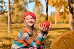Herbstporträt des glücklichen Mädchens im roten Hut und in der Strickjacke lizenzfreie stockfotos