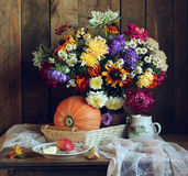 Herbststillleben im rustikalen Artkürbis und in einem Blumenstrauß Lizenzfreies Stockfoto