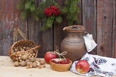 Herbststillleben im ukrainischem ArtTongefäß und Herbstbeere und -gemüse auf altem hölzernem Hintergrund, Nahaufnahme Stockfotografie