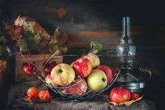 Herbststillleben von Äpfeln in einem Korb mit einer Lampe und Kerzen Stockbild