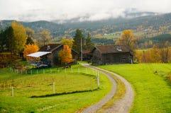 Herbststraße über Bauernhofwiese in Telemark, Norwegen Lizenzfreie Stockbilder