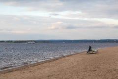 Herbststrand auf dem Volga Die einsame Frauenfigur auf der Bank Die Stadt von Samara, Russland Lizenzfreie Stockfotografie