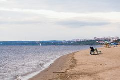 Herbststrand auf dem Volga Die einsame Frauenfigur auf der Bank Die Stadt von Samara, Russland Lizenzfreie Stockfotos